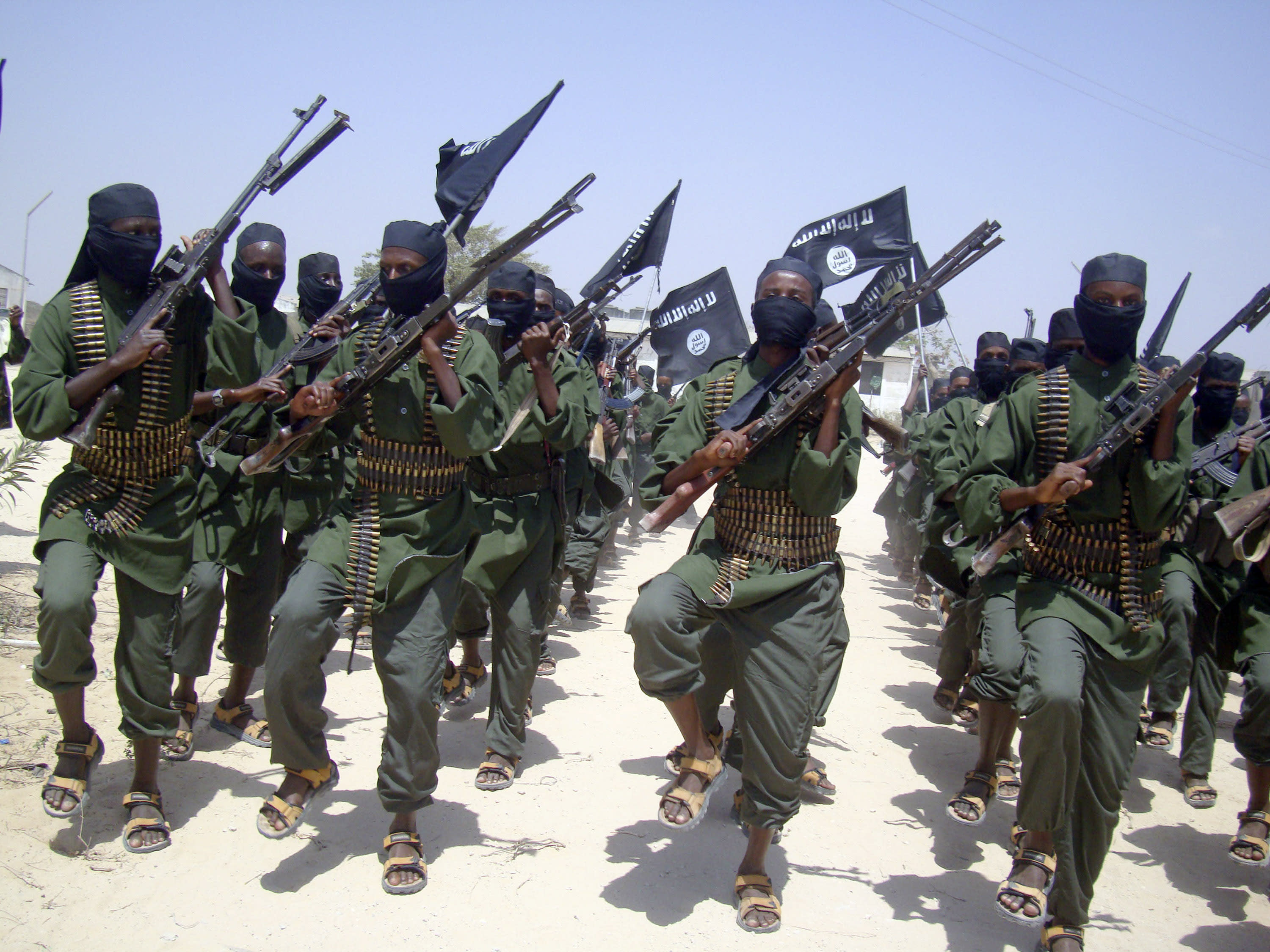 FILE - In this Thursday, Feb. 17, 2011 file photo, al-Shabab fighters march with their weapons during military exercises on the outskirts of Mogadishu, Somalia. Foreign military forces carried out a pre-dawn strike Saturday, Oct. 5, 2013 against foreign fighters in the same southern Somalia village where U.S. Navy SEALS four years ago killed a most-wanted al-Qaida operative, officials said. (AP Photo/Mohamed Sheikh Nor, File)