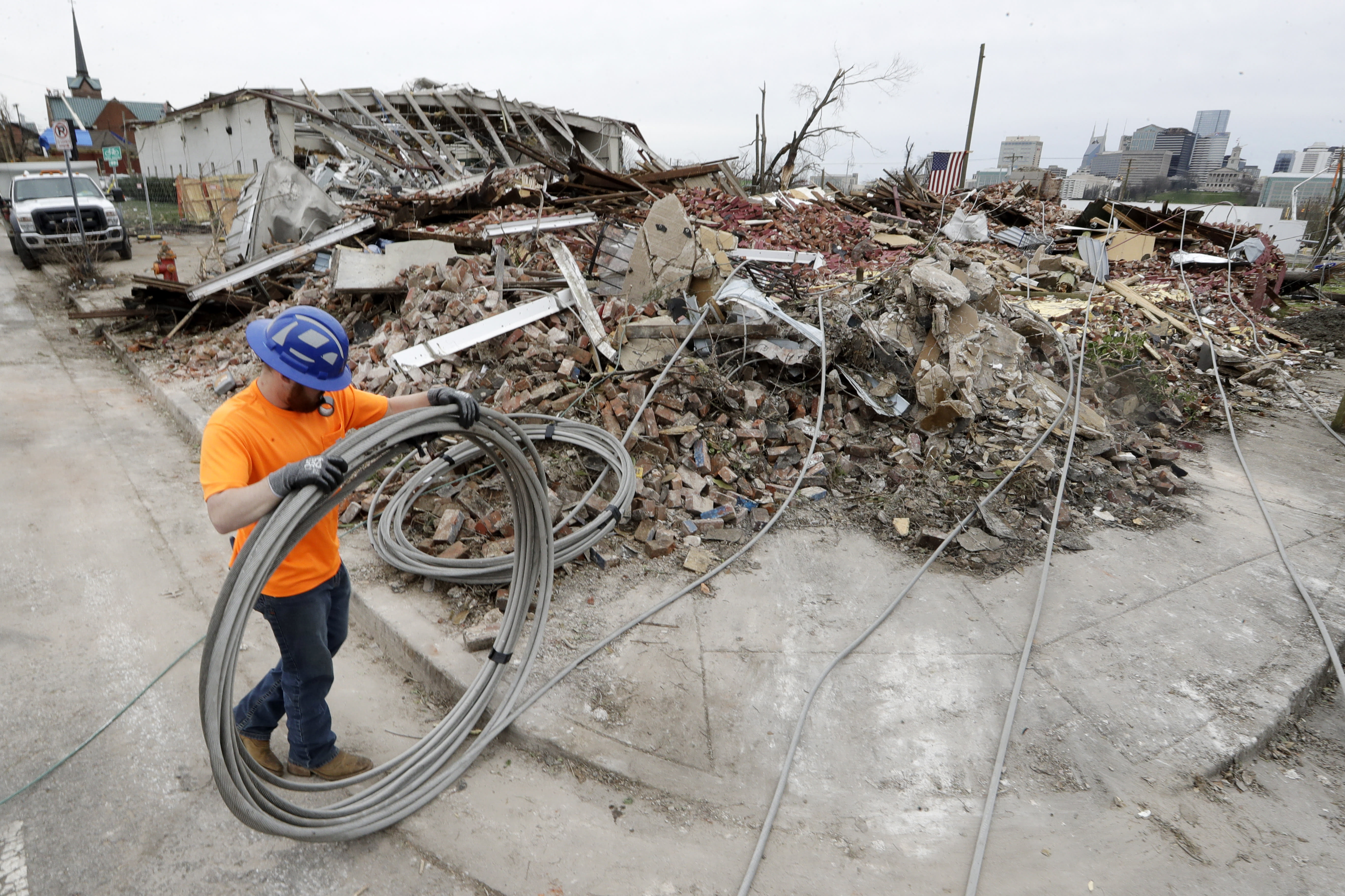 Electrical worker Tyler Morris rolls up damaged power cable Wednesday, March 4, 2020, near a store destroyed by a storm in Nashville, Tenn. After tornadoes hit the state Tuesday, the search for victims continues along with the start of the cleanup from the deadly storms that killed multiple people and left others still missing. (AP Photo/Mark Humphrey)