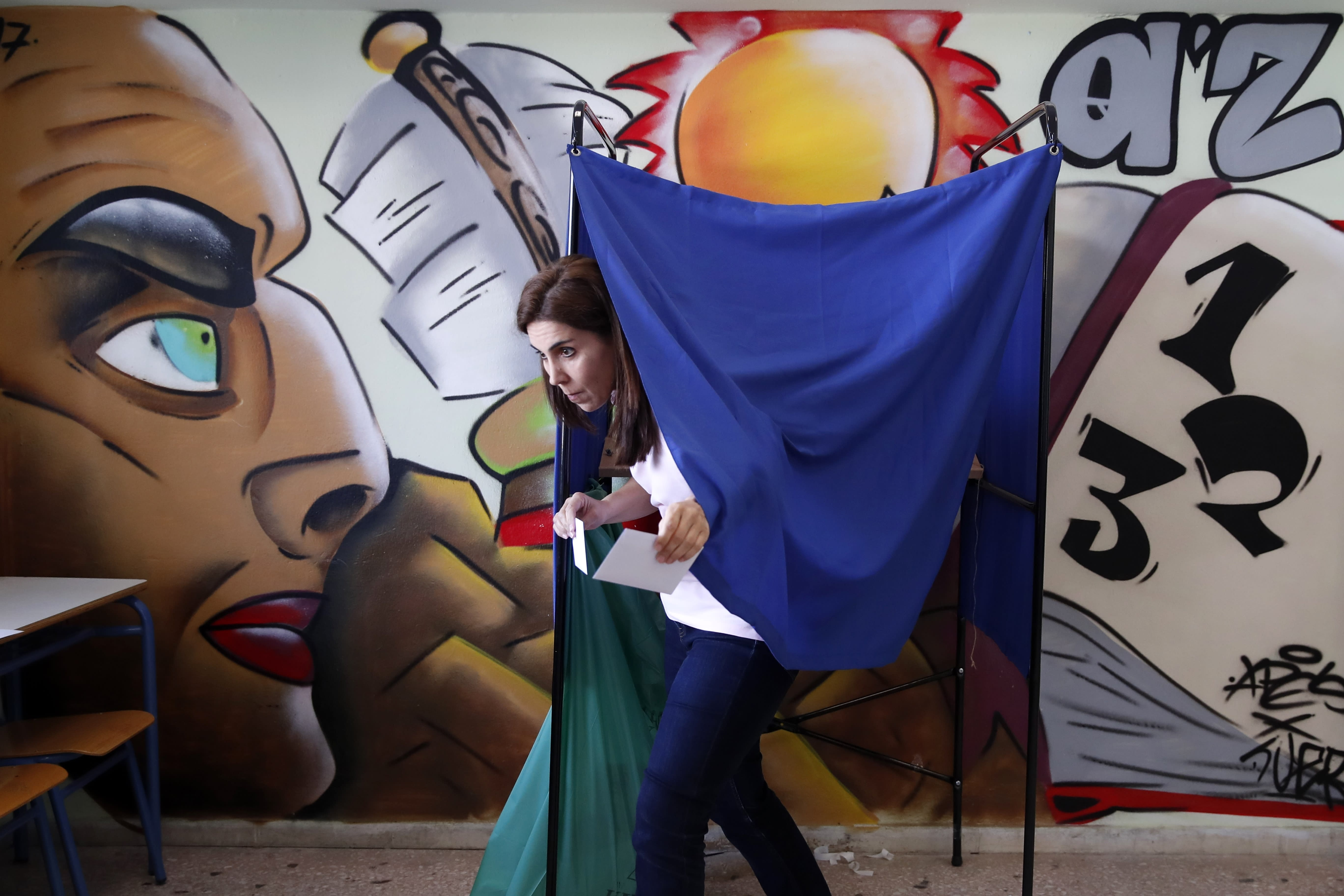 A woman casts his vote at a polling station in Athens on Sunday, May 26, 2019. Polls opened early Sunday in Greece, with nearly 10 million registered voters called upon to vote for the European Parliament, regional and local councils in 39,063 polling stations across the country. (AP Photo/Thanassis Stavrakis)