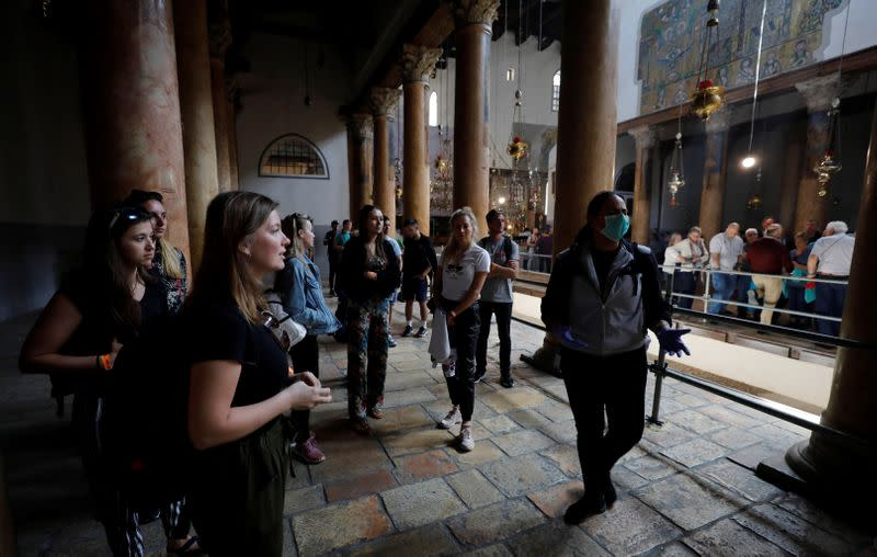 A tourist wearing a mask as a preventive measure against the coronavirus gestures as she visits the Church of the Nativity in Bethlehem in the Israeli-occupied West Bank