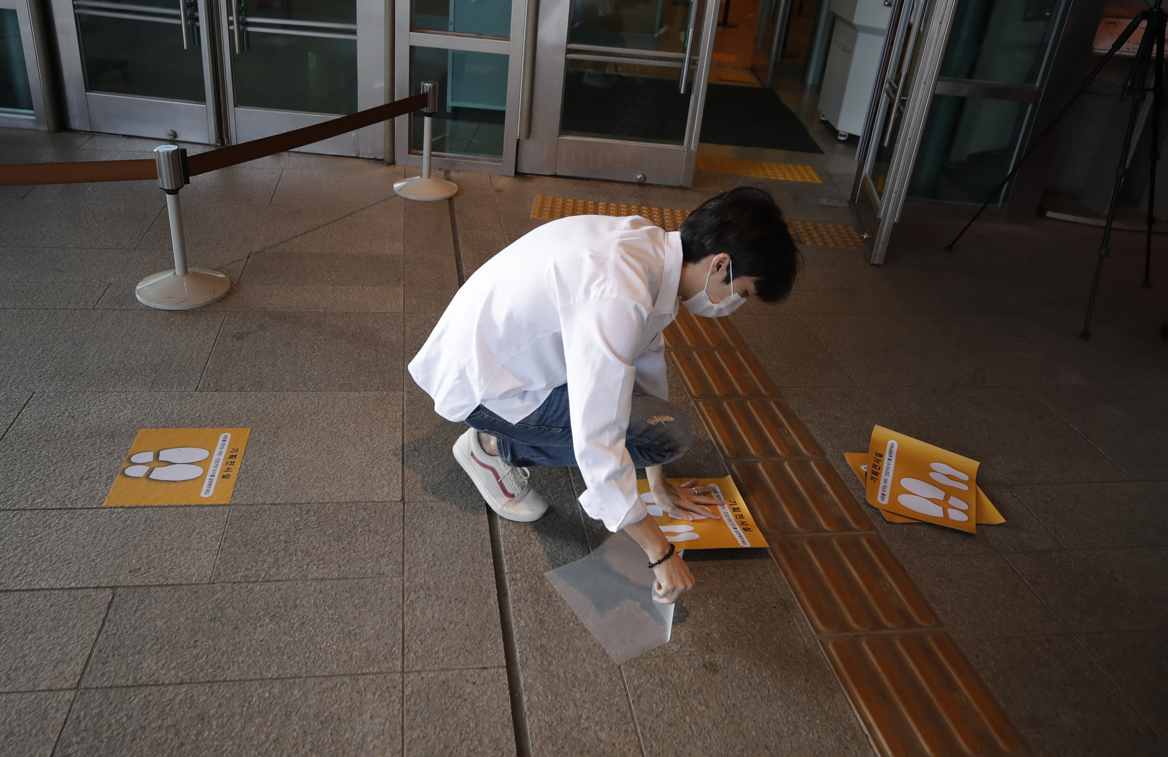 A man wearing a face mask attaches social distancing signs on the floor at the National Museum of Korea in Seoul, South Korea, Monday, Sept. 28, 2020. The museum reopened Monday after having been closed for six weeks as a precaution against the coronavirus. (AP Photo/Lee Jin-man)