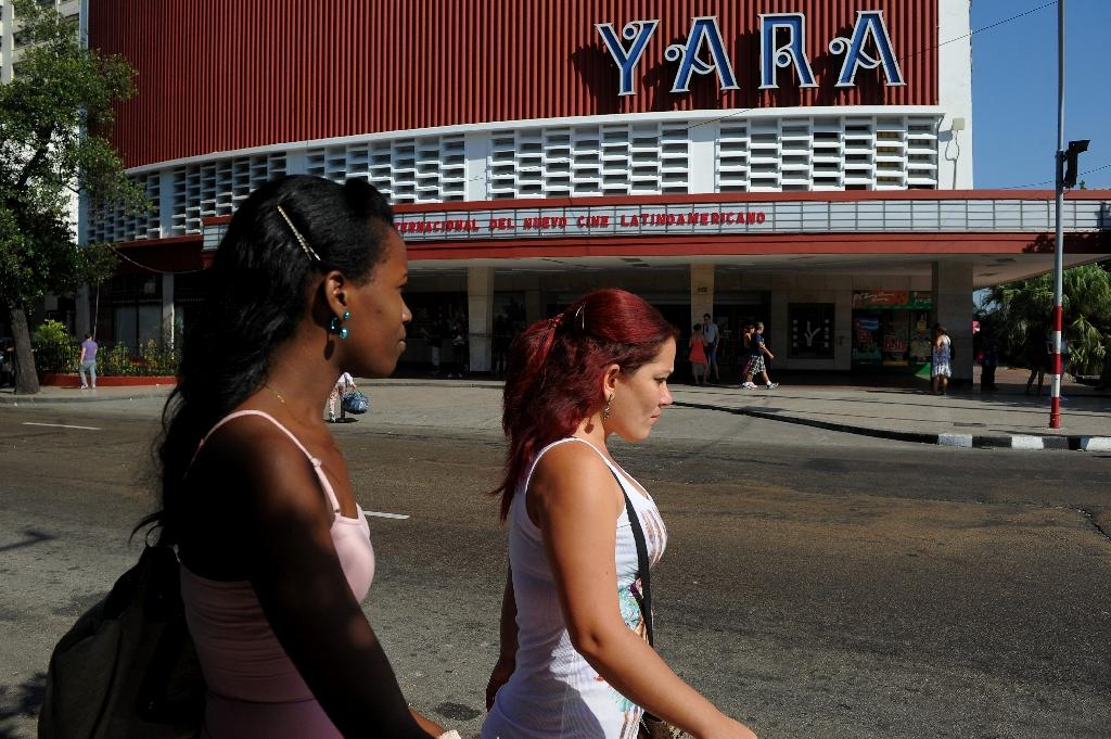 Cubans walk past a movie theater announcing the Havana Latin American Film Festival