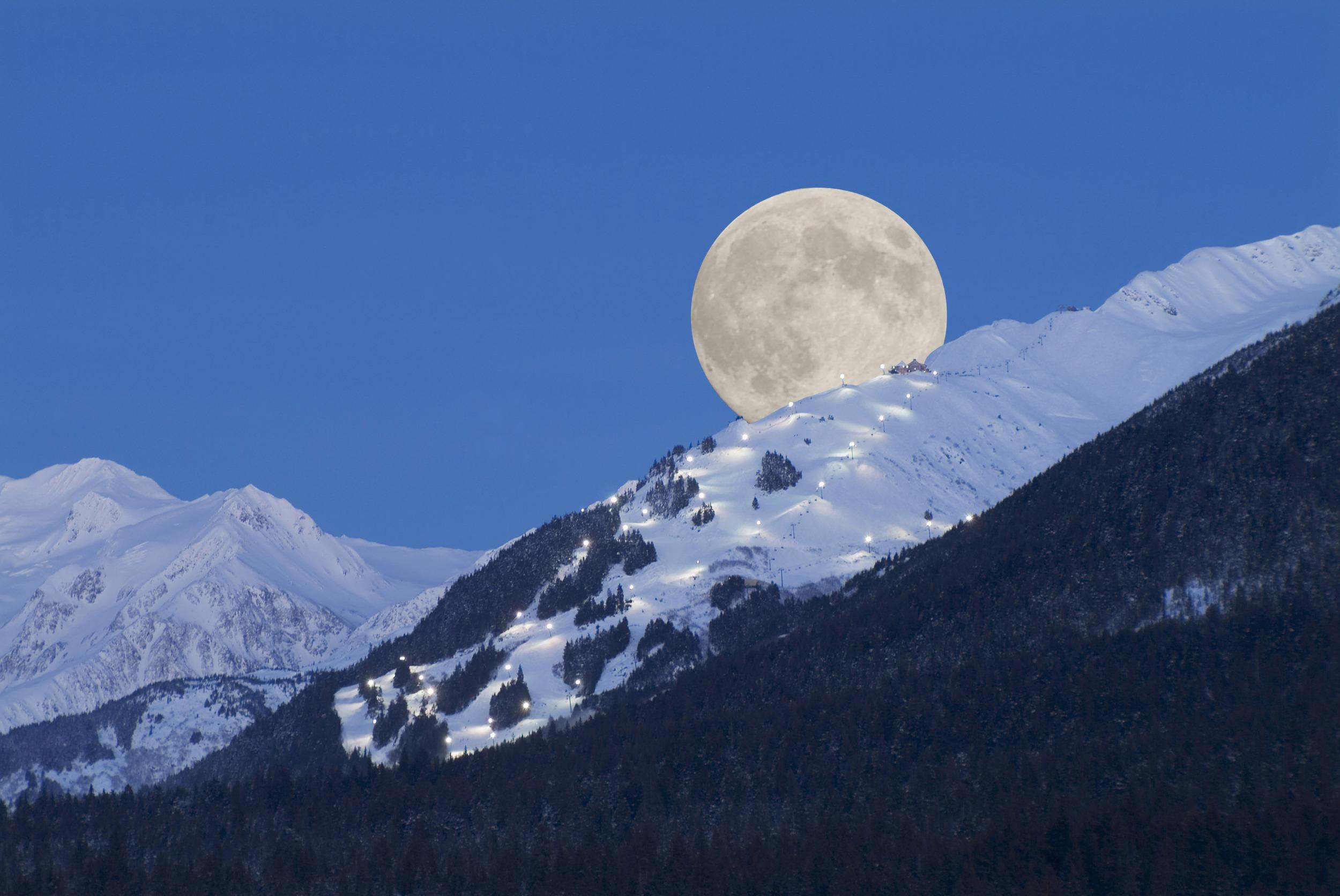 Full moon rising over the Alyeska ski resort in Alaska, USA.