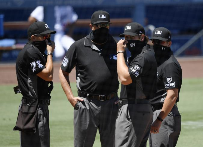 LOS ANGELES, CA - AUGUST 09: Major League umpires wearing face mask prepare to call the game between the San Francisco Giants and Los Angeles Dodgers at Dodger Stadium on August 9, 2020 in Los Angeles, California. The 2020 regular season has been shortened to 60 games and fans are not allowed in the stadium due to the COVID-19 pandemic. (Photo by Kevork Djansezian/Getty Images)