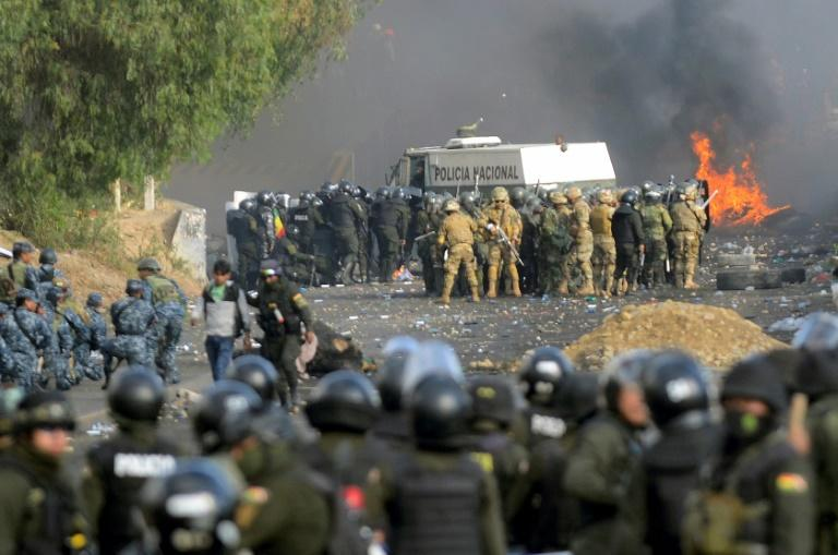 Bolivian riot police and soldiers clash with supporters of ex-President Evo Morales during a protest in the Cochabamba department on November 15