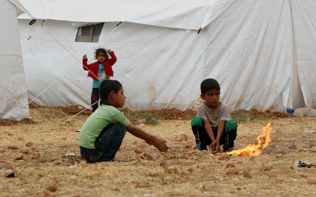 Children sit near a fire in front of tents housing displaced Syrians in a camp on the southern outskirts of the northern Syrian city of Aleppo on October 22, 2015 (AFP Photo/Fadi al-Halabi)