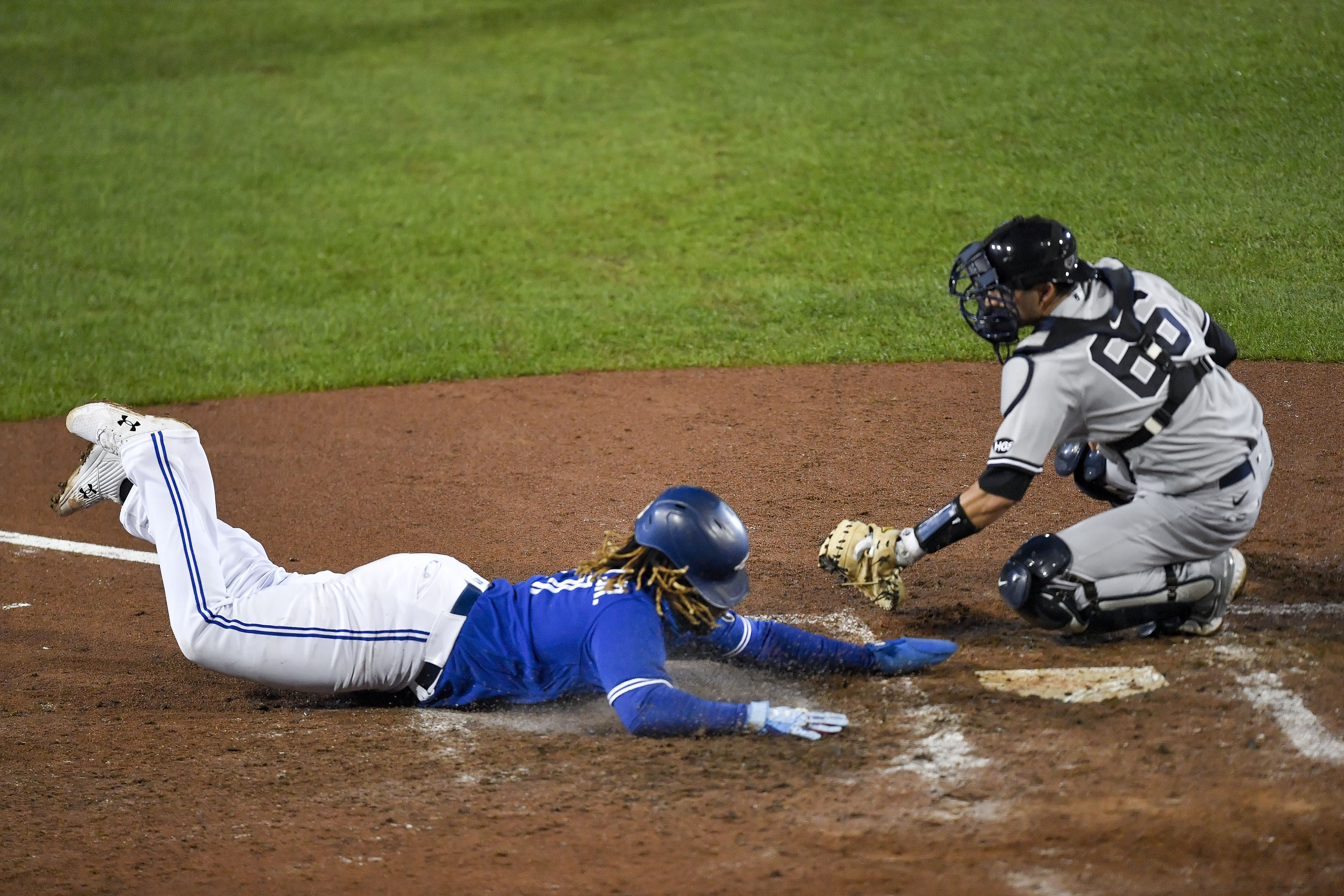 Toronto Blue Jays' Vladimir Guerrero Jr. scores as New York Yankees catcher Kyle Higashioka reaches to make a tag, on a double by Alejandro Kirk during the sixth inning of a baseball game in Buffalo, N.Y., Thursday, Sept. 24, 2020. (AP Photo/Adrian Kraus)