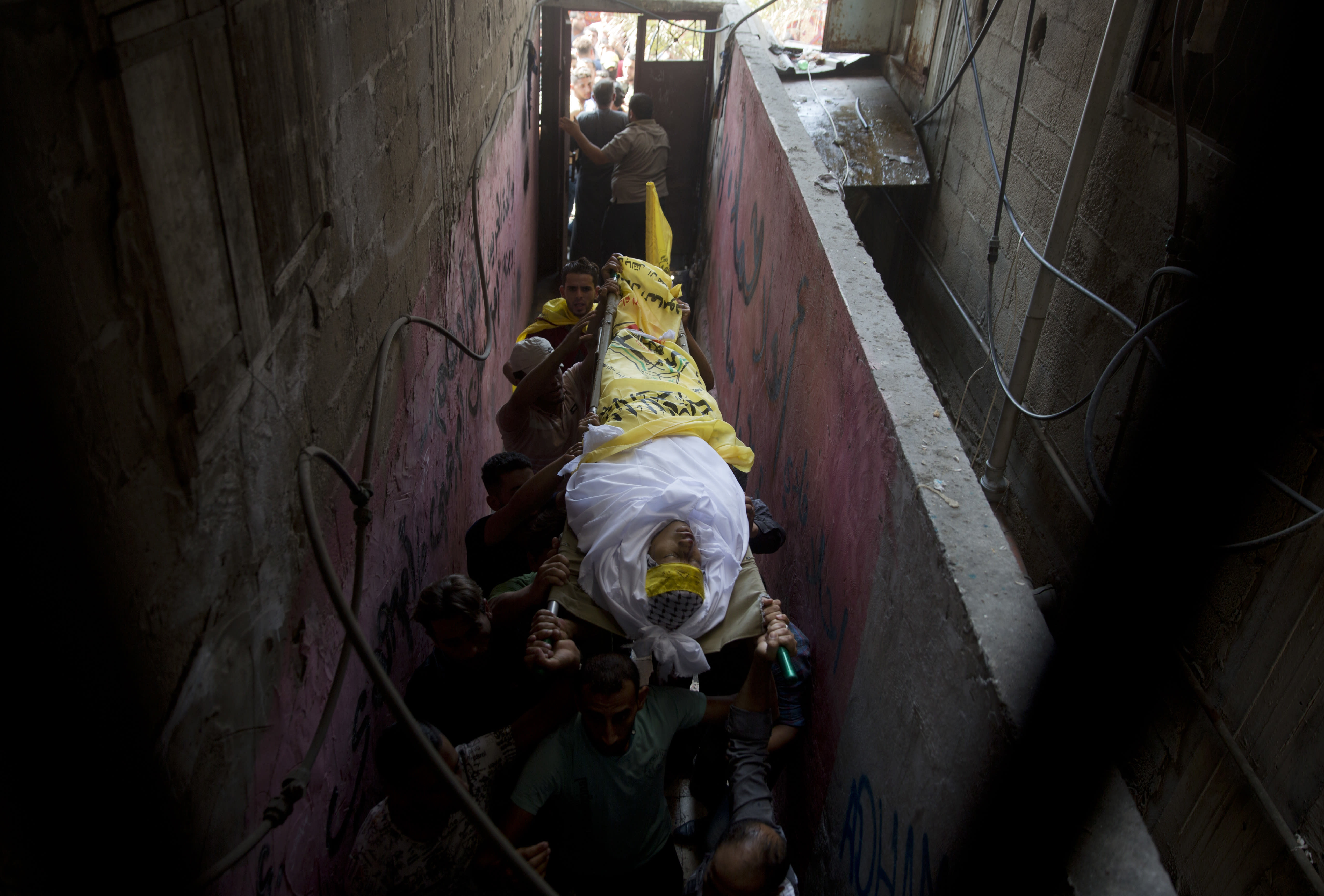 Palestinian carry the body of Mohammed Abbas, 21, who was killed by Israeli troops during Friday's protest at the Gaza Strip's border with Israel, into the family home during his funeral in Gaza City, Saturday, Oct. 13, 2018. (AP Photo/Khalil Hamra)