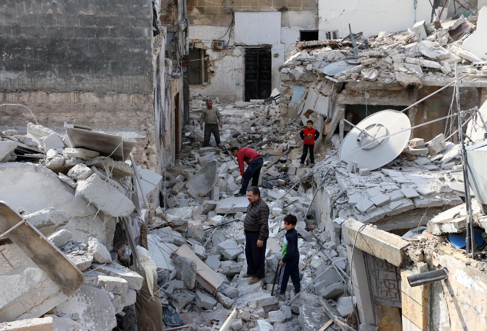 Syrians search through the rubble of buildings for re-usable items in the Kalasa neighbourhood of Aleppo on October 28, 2014 (AFP Photo/Baraa al-Halabi)