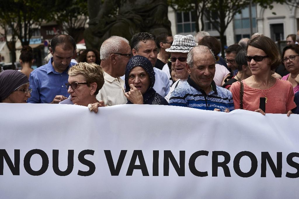 """People hold a banner reading """"We will overcome"""" as they take part in a silent march on July 30, 2016 in Lyon following the fatal attack on a French priest (AFP Photo/Jean-Philippe Ksiazek )"""