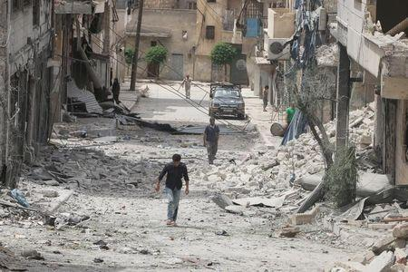 People walk on the rubble of damaged buildings after an airstrike in the rebel held area of Aleppo's Baedeen district