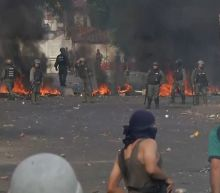Venezuelan soldiers defect as troops fire tear gas at protesters on Colombia border