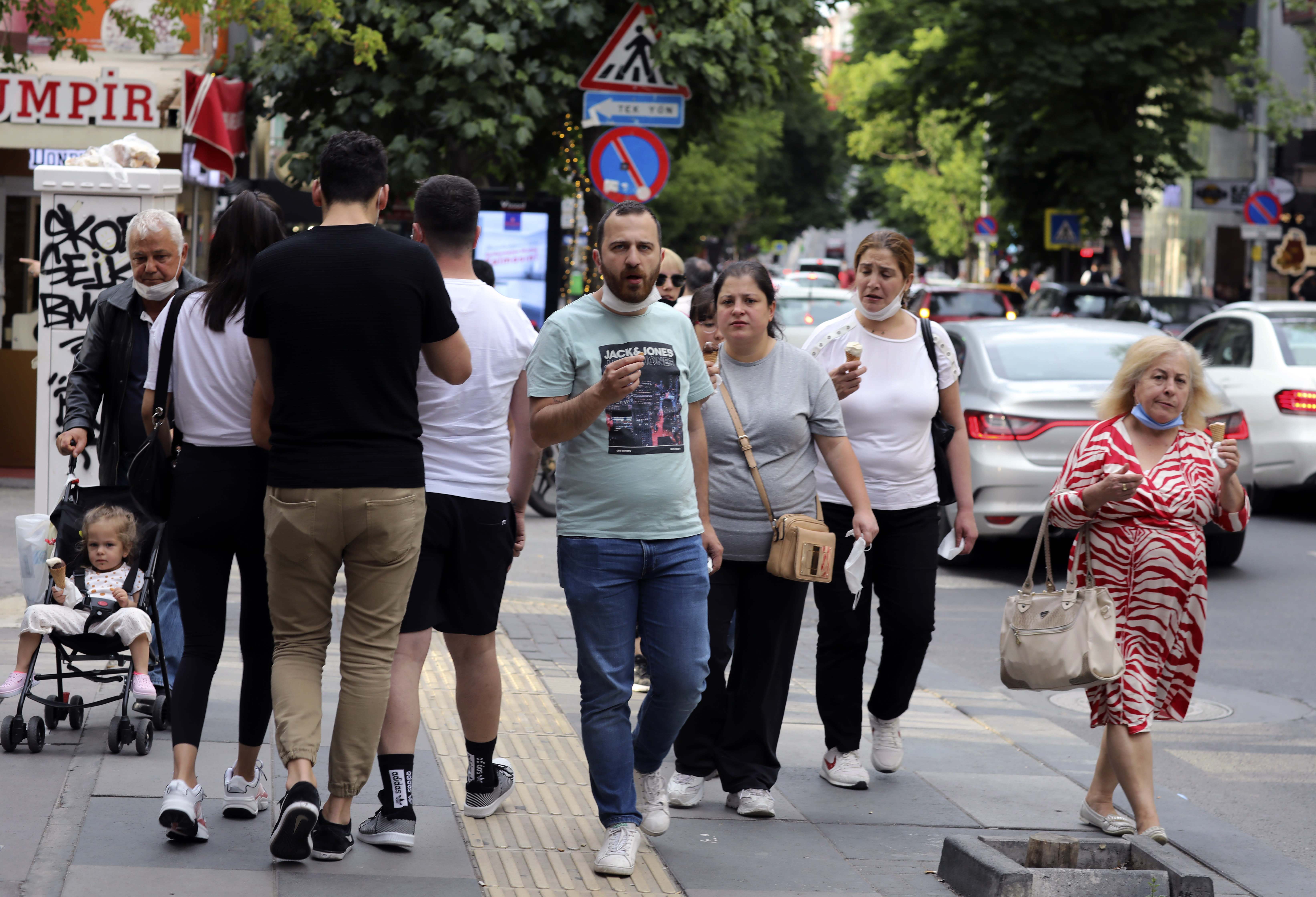 People who are not wearing face masks to protect against the spread of coronavirus, walk in city the centre, in Ankara, Turkey, Sunday, June 21, 2020. Turkish authorities have made the wearing of masks mandatory in three major cities to curb the spread of COVID-19 following an uptick in confirmed cases since the reopening of many businesses.(AP Photo/Burhan Ozbilici)