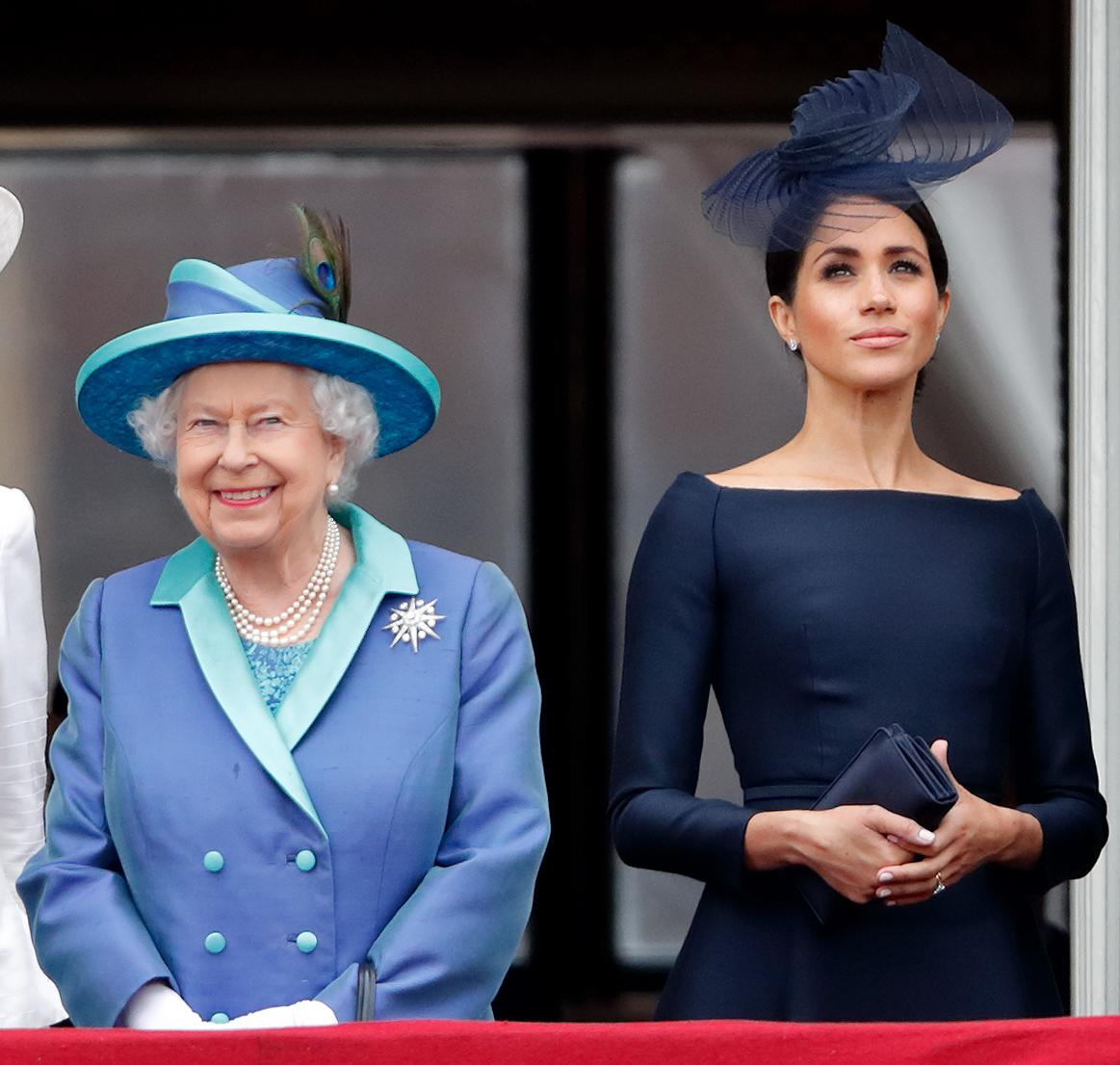 LONDON, UNITED KINGDOM - JULY 10: (EMBARGOED FOR PUBLICATION IN UK NEWSPAPERS UNTIL 24 HOURS AFTER CREATE DATE AND TIME) Queen Elizabeth II and Meghan, Duchess of Sussex watch a flypast to mark the centenary of the Royal Air Force from the balcony of Buckingham Palace on July 10, 2018 in London, England. The 100th birthday of the RAF, which was founded on on 1 April 1918, was marked with a centenary parade with the presentation of a new Queen's Colour and flypast of 100 aircraft over Buckingham Palace. (Photo by Max Mumby/Indigo/Getty Images)