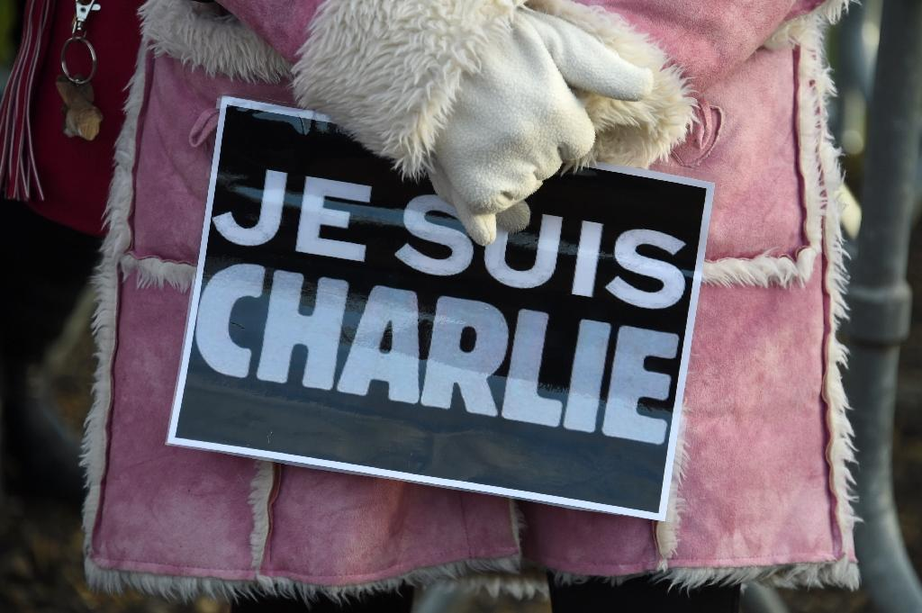 "A woman holds a placard reading ""Je suis Charlie"" (I am Charlie) during the funeral of French cartoonist and Charlie Hebdo editor Stephane ""Charb"" Charbonnier, on January 16, 2015 in Pontoise, outside Paris"