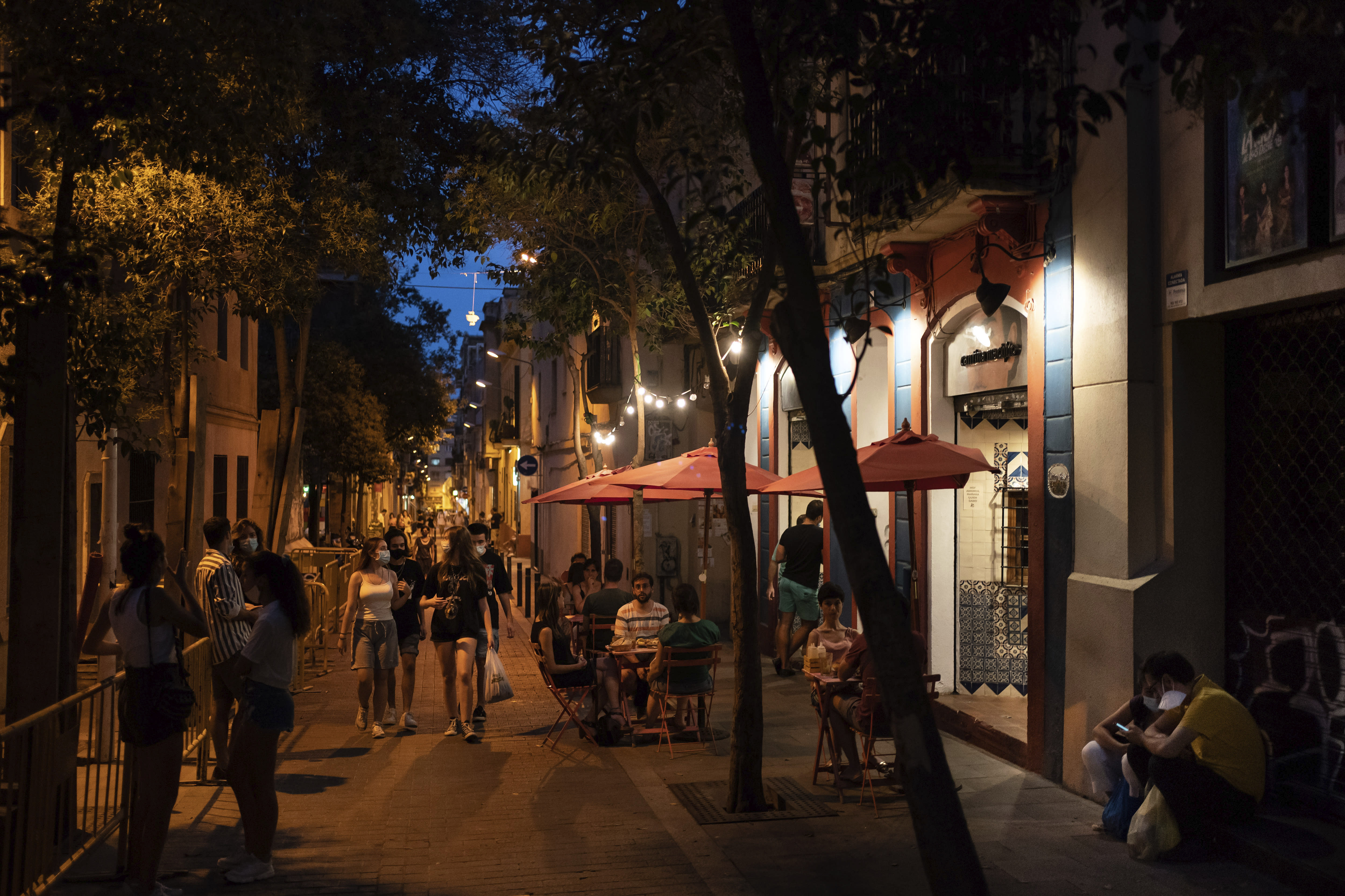 People gather outside a restaurant at night in Gracia neighborhood in Barcelona, Spain, Friday, July 24, 2020. Health authorities in the northeastern region of Catalonia have ordered nightclubs to be fully closed and bars and restaurant in Barcelona to shut down by midnight in an effort to stem the spread of the new coronavirus. (AP Photo/Felipe Dana)