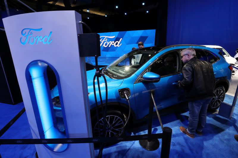 A visitor views a hybrid Ford Escape FWD small SUV at the Canadian International Auto Show in Toronto
