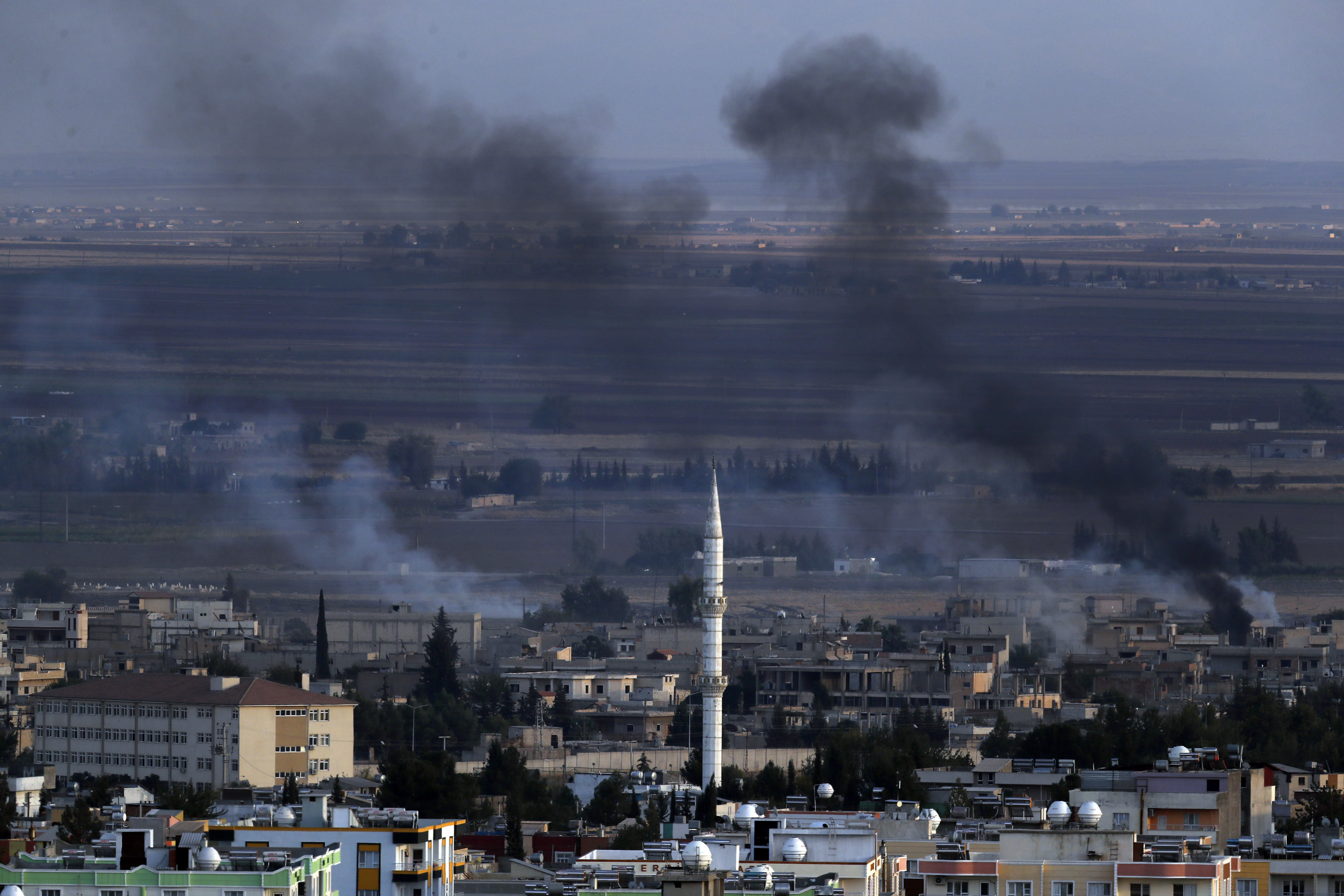 In this photo taken from the Turkish side of the border between Turkey and Syria, in Ceylanpinar, Sanliurfa province, southeastern Turkey, smoke billows from targets in Ras al-Ayn, Syria, caused by bombardment by Turkish forces, Tuesday, Oct. 15, 2019. Turkish artillery on Tuesday pounded suspected Syrian Kurdish positions near the town in northeast Syria amid reports that Kurdish fighters had retaken the town as Turkey pressed ahead with a military incursion that has drawn widespread condemnation. (AP Photo/Lefteris Pitarakis)