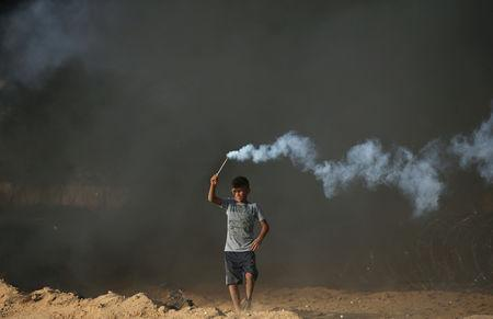 A Palestinian boy holds a tear gas canister fired by Israeli troops during a protest calling for lifting the Israeli blockade on Gaza and demanding the right to return to their homeland, at the Israel-Gaza border fence in the southern Gaza Strip October 5, 2018. REUTERS/Ibraheem Abu Mustafa
