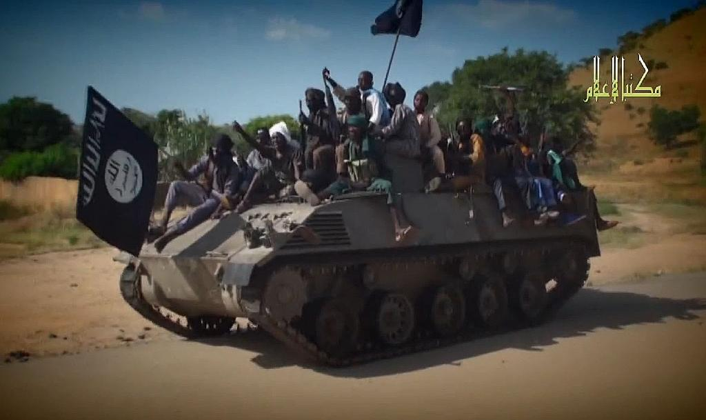 A screengrab taken on November 9, 2014 from a Boko Haram video released by the Islamist extremist group shows Boko Haram fighters parading on a tank in an unidentified town (AFP Photo/)