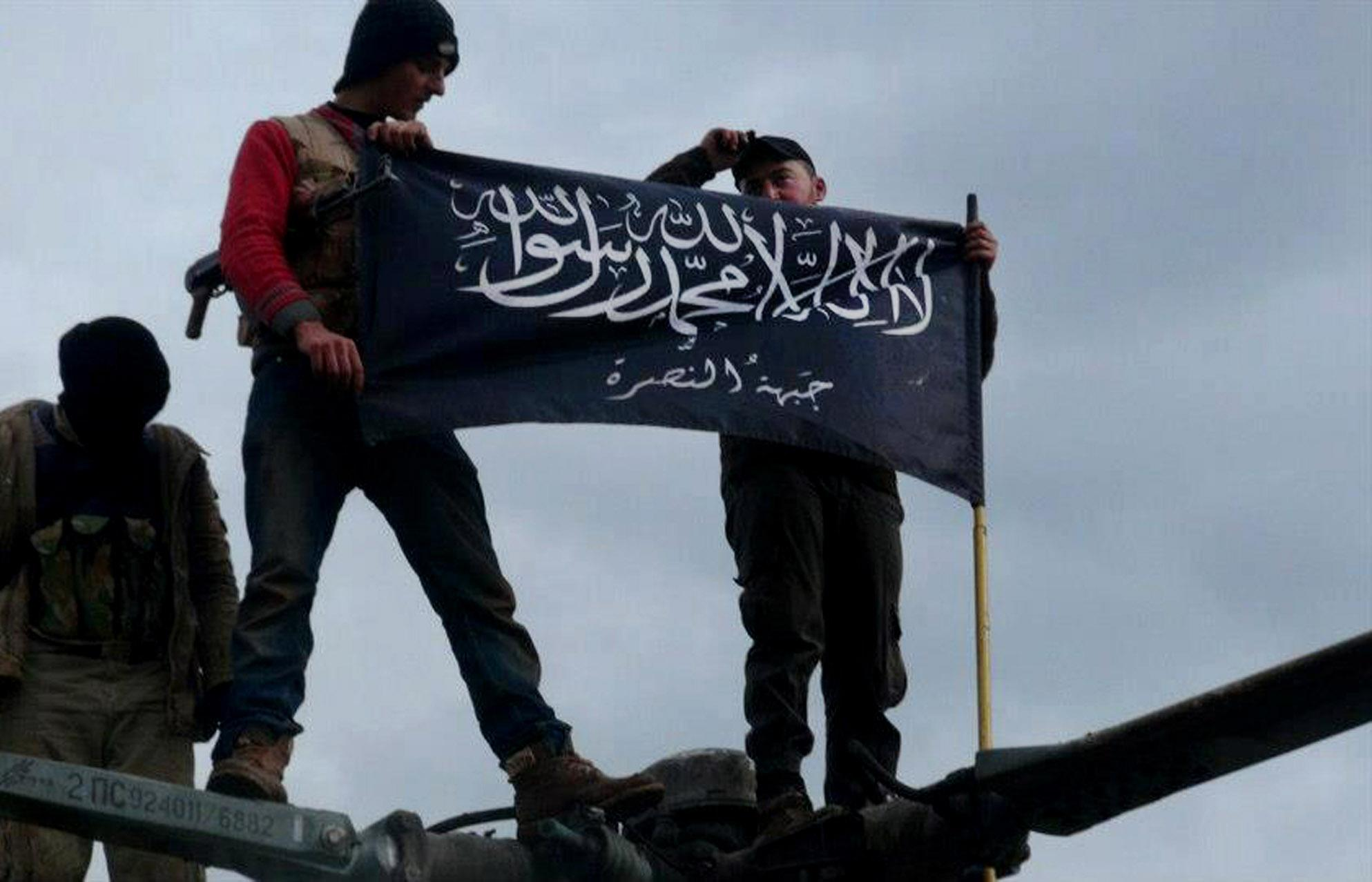 """FILE - In this Friday, Jan. 11, 2013 file citizen journalism image provided by Edlib News Network, ENN, which has been authenticated based on its contents and other AP reporting, shows rebels from al-Qaida affiliated Jabhat al-Nusra waving their brigade flag on the top of a Syrian air force helicopter, at Taftanaz air base that was captured by the rebels, in Idlib province, northern Syria. Al-Qaida's branch in Iraq said it has merged with Syria's extremist Jabhat al-Nusra, a move that shows the rising confidence of radicals within the Syrian rebel movement and is likely to trigger renewed fears among its international backers. Arabic on the flag reads, """"There is no God only God and Mohamad his prophet, Jabhat al-Nusra."""" (AP Photo/Edlib News Network ENN, File)"""