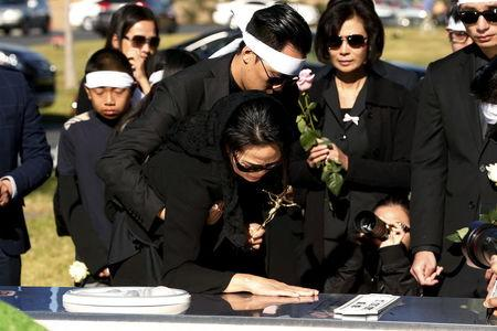 Van Thanh Nguyen (C) touches the burial vault of her daughter, San Bernardino shooting victim Tin Nguyen, during her funeral at Good Shepherd Cemetery in Huntington Beach, California December 12, 2015. REUTERS/Patrick T. Fallon -
