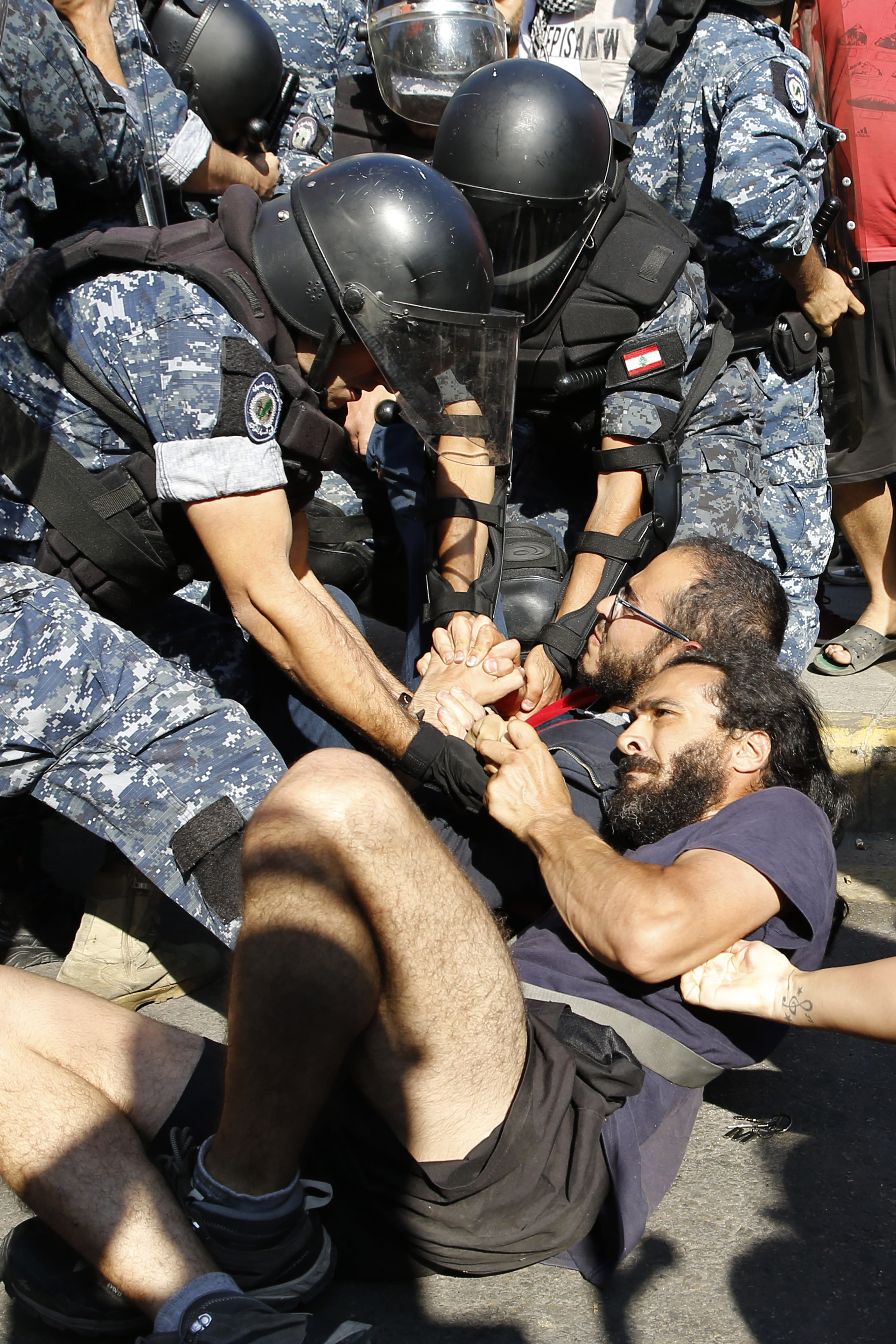 Anti-government protesters lie on a road holding each other as riot police try to remove them and open the road, in Beirut, Lebanon, Thursday, Oct. 31, 2019. Army units and riot police took down barriers and tents set up in the middle of highways and major intersections Thursday. (AP Photo/Bilal Hussein)