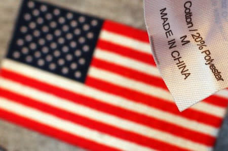 "The label reading ""Made in China"" on a sweatshirt is seen over another shirt with a U.S. flag at a souvenir stand in Boston"