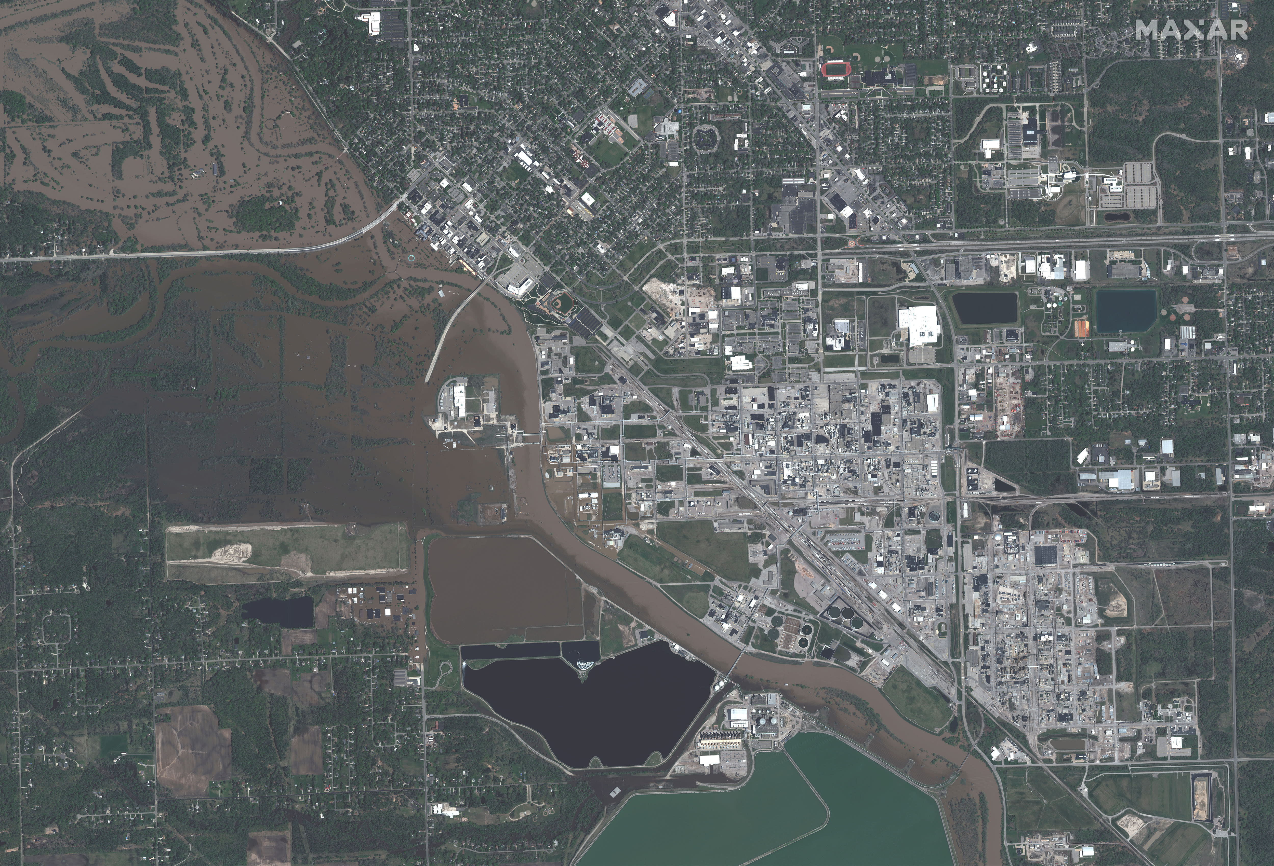This photo provided by Maxar Technologies shows an overview of Midland, Mich., Thursday, May 21, 2020, with floodwaters along the Tittabawassee River. (Maxar Technologies via AP)