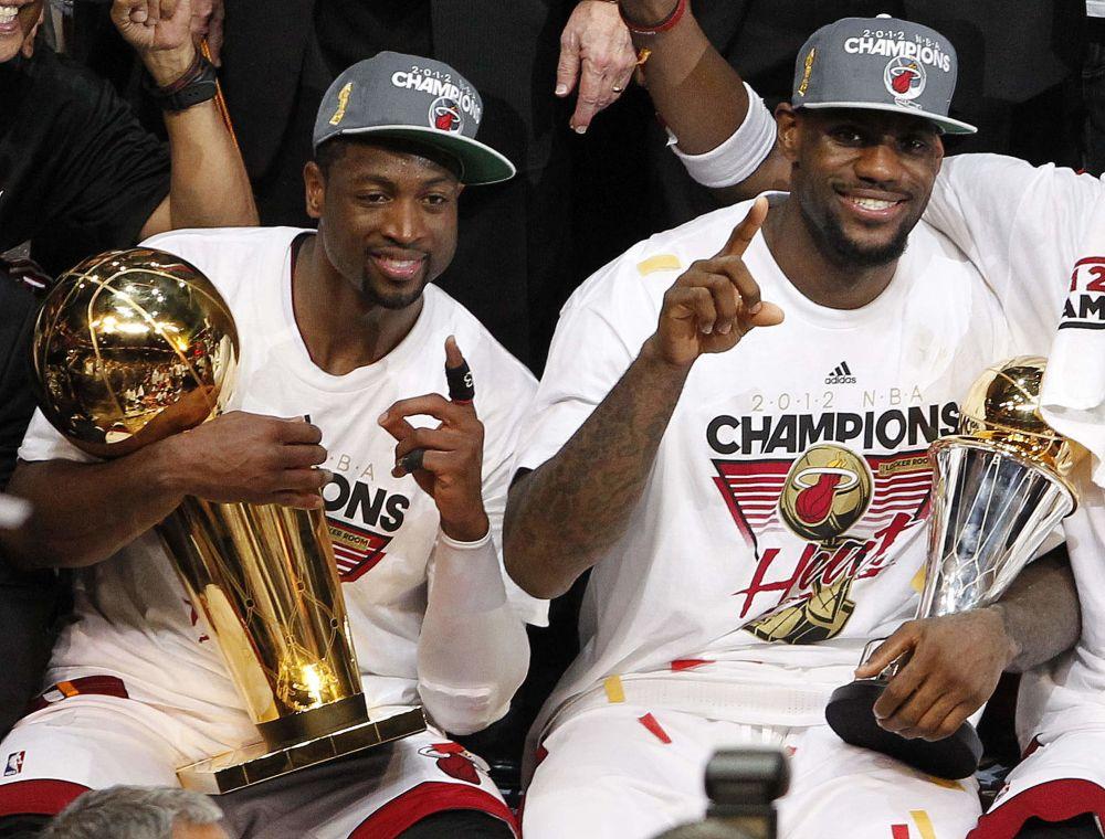 Dwyane Wade, del Heat de Miami, izquierda, posa con el Trofeo Larry O'Brien NBA del Campeonato de la NBA, mientras su compañero LeBron James sostiene su trofeo a Jugador Más Valioso, después de derrotar en la serie final de la liga al Thunder de Oklahoma, el jueves 21 de junio de 2012, en Miami.  (Foto AP/Lynne Sladky)