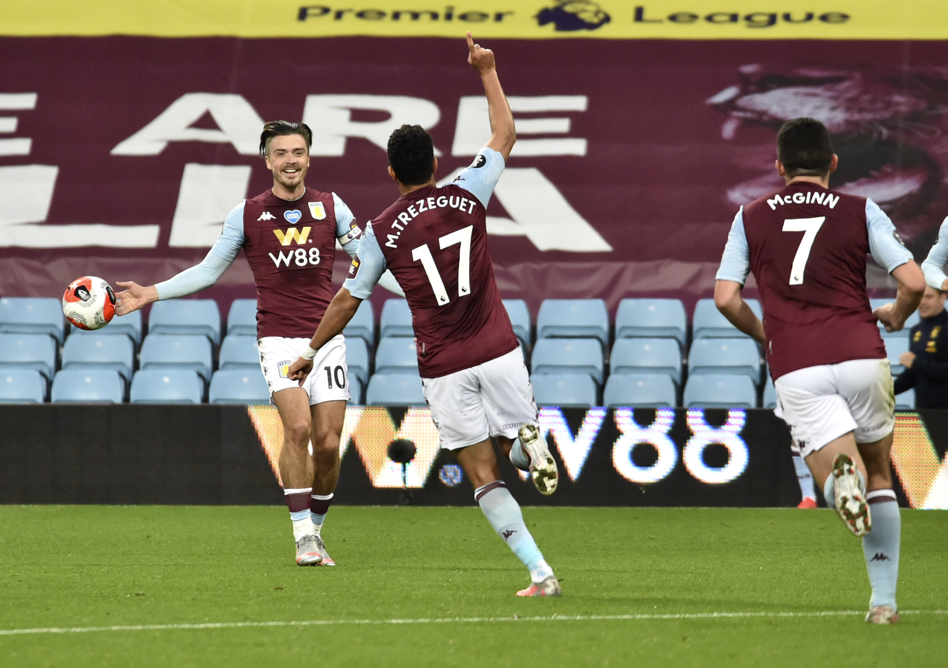 Aston Villa's Trezeguet, centre, celebrates with teammate Jack Grealish, left, after scoring his team's first goal during the English Premier League soccer match between Aston Villa and Arsenal at Villa Park in Birmingham, England, Tuesday, July 21, 2020. (AP Photo/Rui Vieira,Pool)