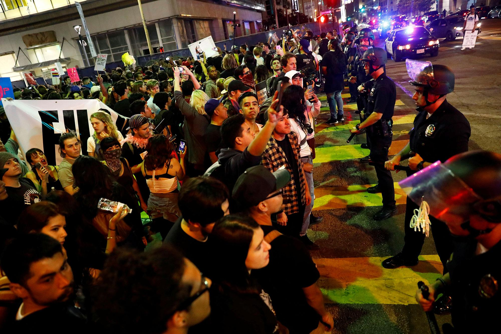 <p>Demonstrators are blocked by an LAPD skirmish line during a march through the streets of downtown Los Angeles in protest following the election of Republican Donald Trump as President of the United States in Los Angeles, Calif., on Nov. 11, 2016. (Photo: Patrick T. Fallon/Reuters) </p>