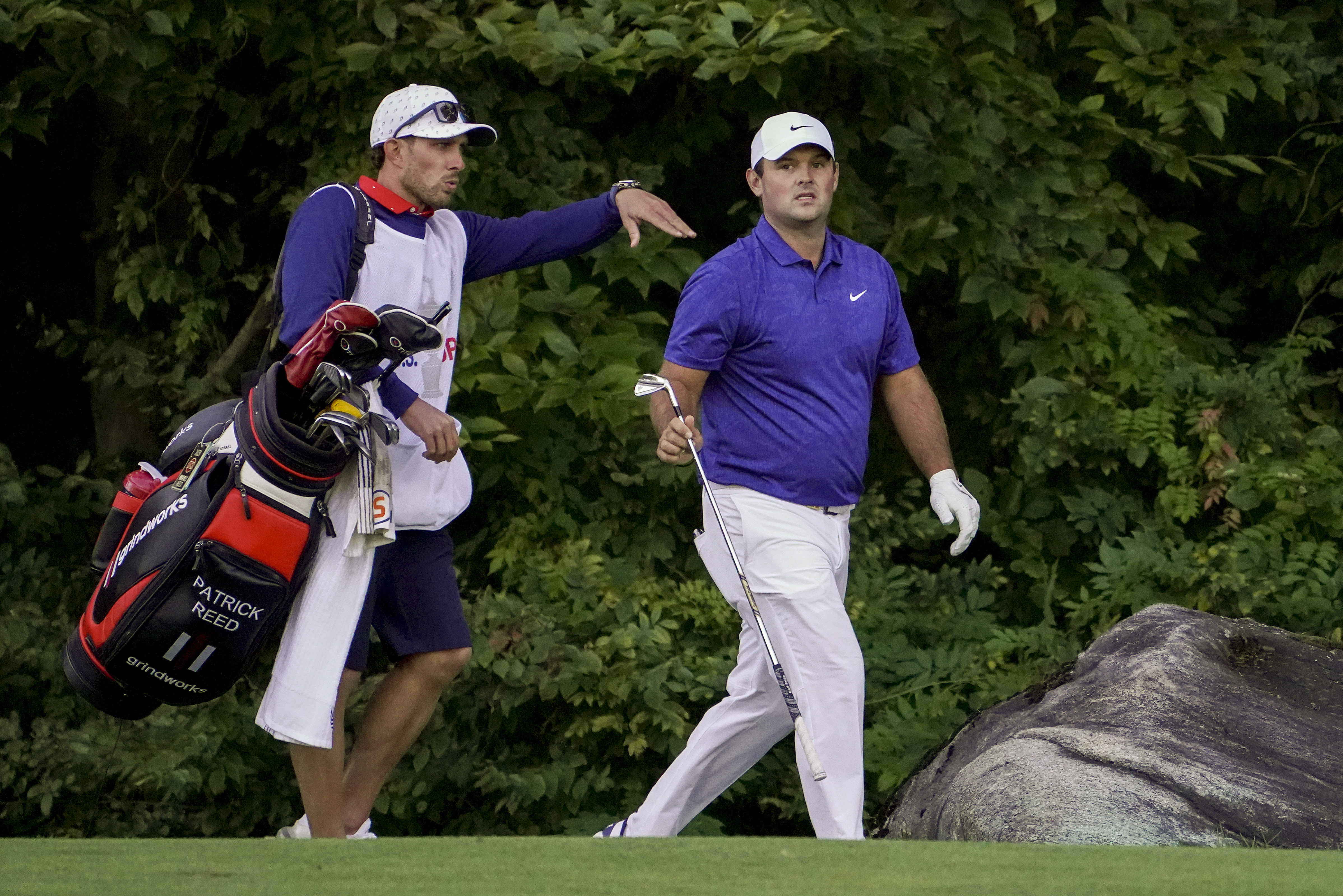 Patrick Reed, of the United States, hands a club to his caddie as they walk along the 15th fairway during the third round of the US Open Golf Championship, Saturday, Sept. 19, 2020, in Mamaroneck, N.Y. (AP Photo/John Minchillo)