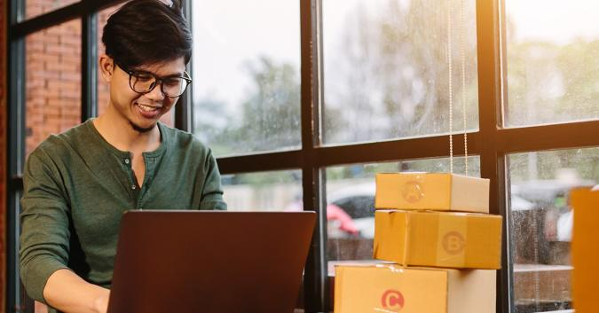 Stock image of a man using a laptop with shipping boxes sitting in the background.