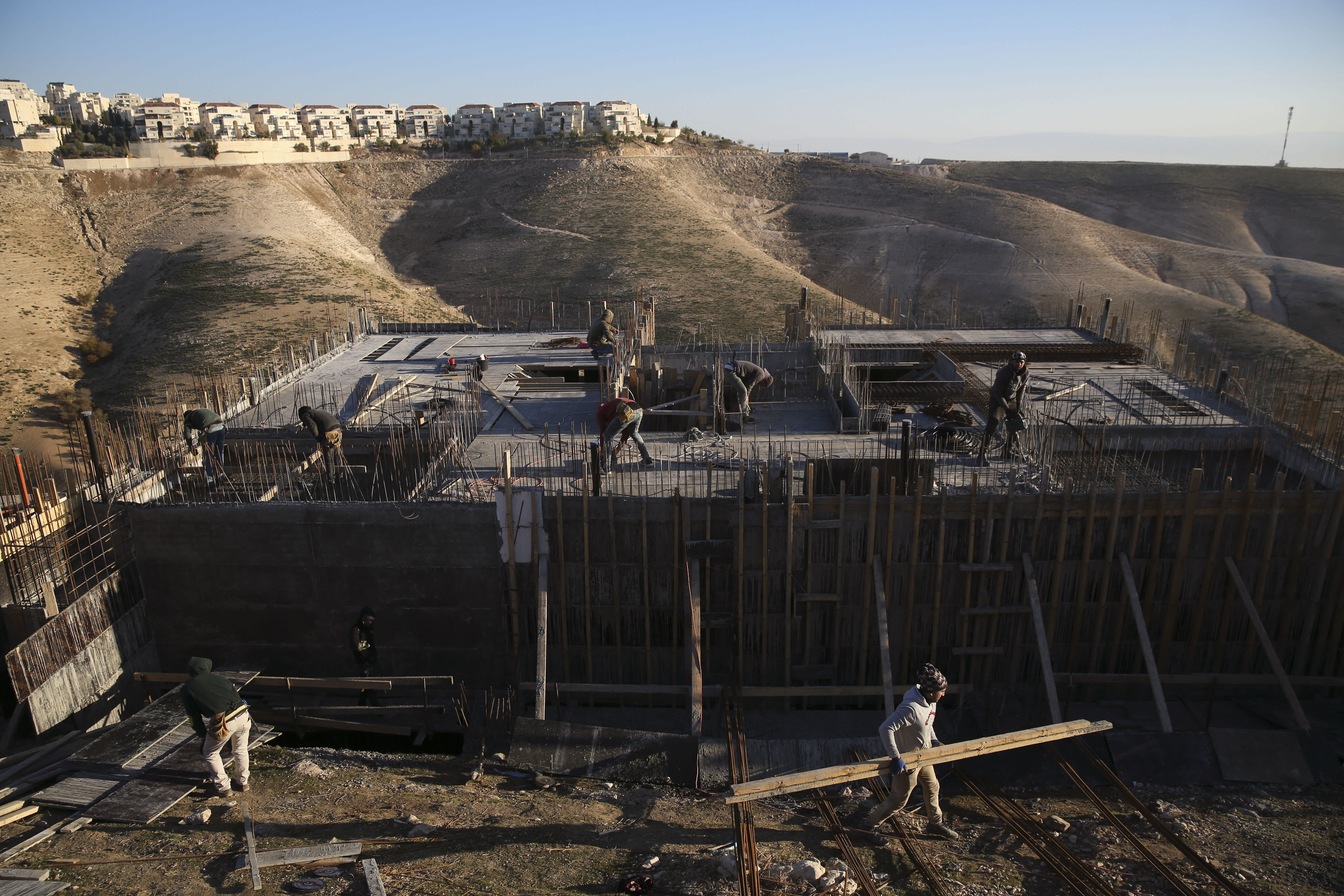 FILE - In this Feb. 7, 2017 file photo, Palestinian laborers work at a construction site in the Israeli settlement of Maale Adumim, near Jerusalem. Israeli authorities have advanced plans to build over 2,100 new settlement homes in the occupied West Bank. Wednesday's development indicates they are pressing ahead with a building boom that has gained steam during the presidency of Donald Trump. (AP Photo/Oded Balilty, File)