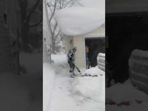 Woman With Shovel vs. Rooftop Full of Snow