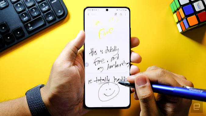 Samsung Galaxy S21 Ultra S Pen. A hand holding the Galaxy S21 Ultra face up with another hand holding a blue S Pen writing on the screen.