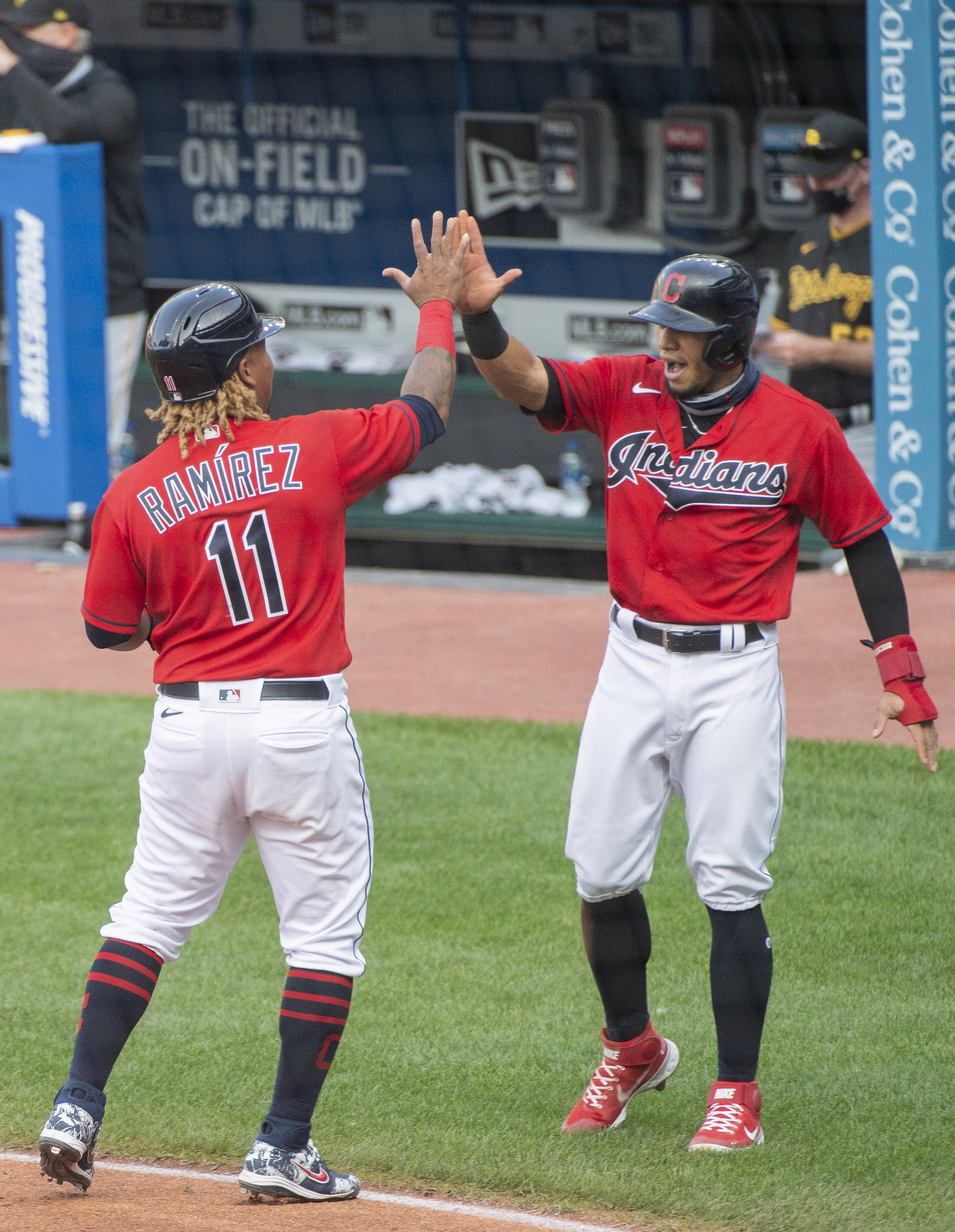 Cleveland Indians' Jose Ramirez (11) celebrates with Cesar Hernandez after scoring on a two-run double by Carlos Santana during the seventh inning of a baseball game against the Pittsburgh Pirates in Cleveland, Sunday, Sept. 27, 2020. (AP Photo/Phil Long)