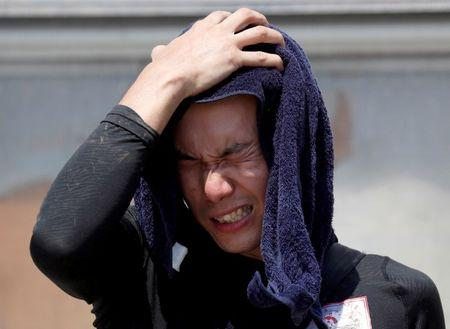 FILE PHOTO: A volunteer, for recovery work, wipes his sweat as he takes a break in a heat wave at a flood affected area in Kurashiki, Okayama Prefecture, Japan, July 14, 2018. REUTERS/Issei Kato/File Photo