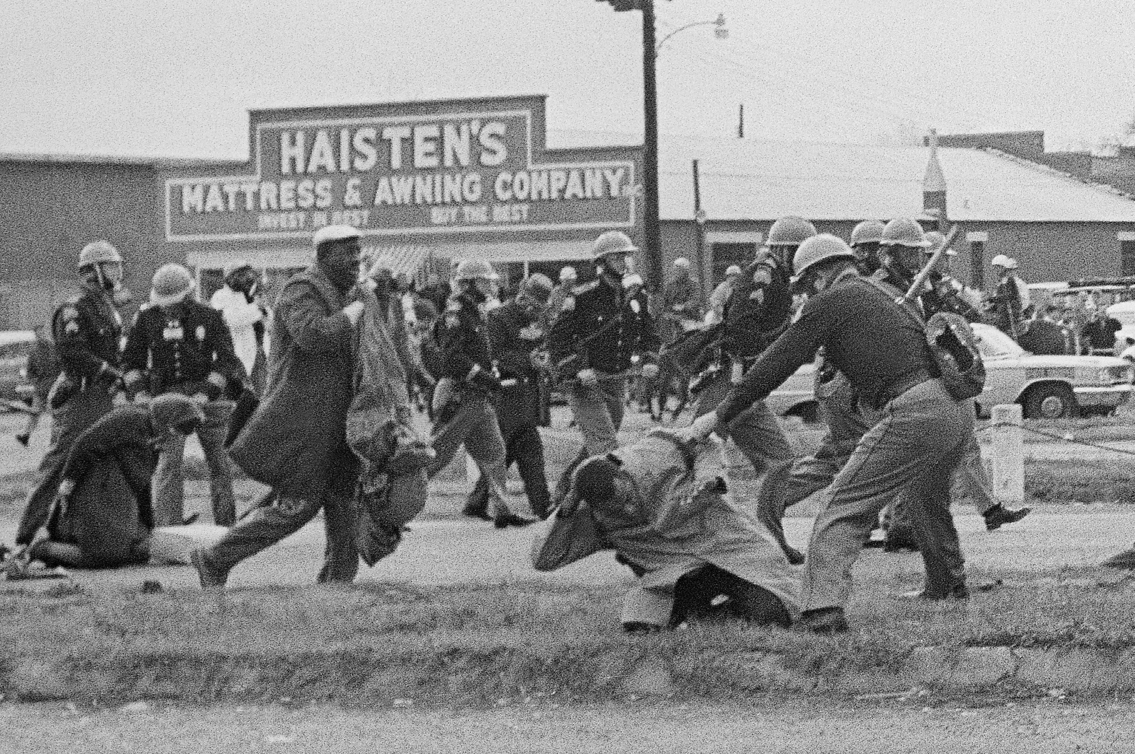 FILE - In this March 7, 1965, file photo, a state trooper swings a billy club at John Lewis, right foreground, chairman of the Student Nonviolent Coordinating Committee, to break up a civil rights voting march in Selma, Ala. Lewis sustained a fractured skull. Lewis, who carried the struggle against racial discrimination from Southern battlegrounds of the 1960s to the halls of Congress, died Friday, July 17, 2020. (AP Photo/File)