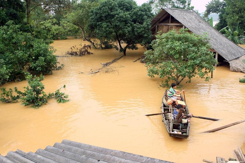 Vietnamese villagers transport boxes of instant noodles after receiving relief aid, past flooded homes in a village in the central province of Ha Tinh, on October 16, 2016 (AFP Photo/-, Vietnam News Agency)