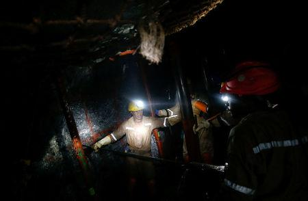 Mine workers employed at Sibanye Gold's Masimthembe shaft operate a drill in Westonaria