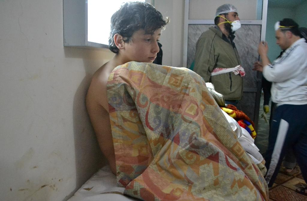 A young man sits on a bed at a clinic in the village of Sarmin, following reports of suffocation cases related to an alleged regime gas attack in the area on March 17, 2015 (AFP Photo/Mohamad Zeen)