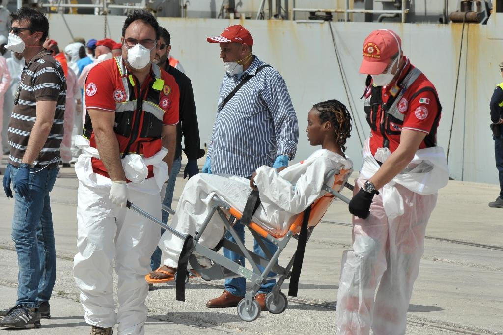A woman rescued at sea by the Italian Navy receives medical assistance after arriving in the Italian port of Reggio Calabria, on May 29, 2016 (AFP Photo/Giovanni Isolino)