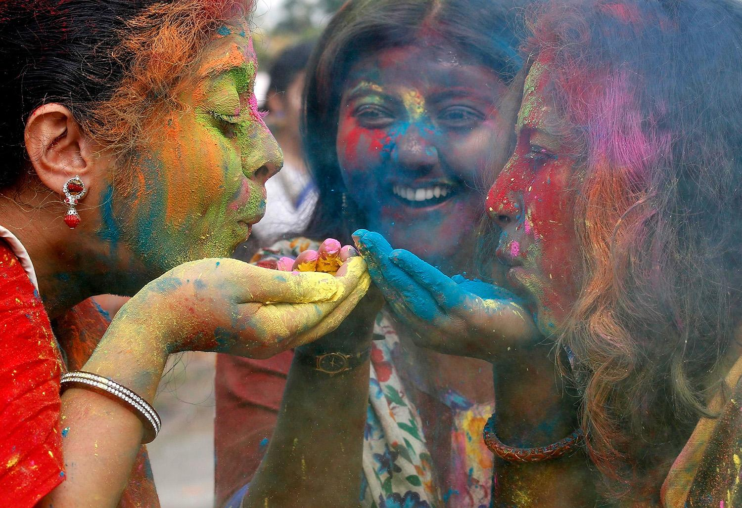 <p>Students of Rabindra Bharati University blow colored powder during Holi, the Festival of Colors, celebrations inside the university campus in Kolkata, India, March 9, 2017. (Rupak De Chowdhuri/Reuters) </p>