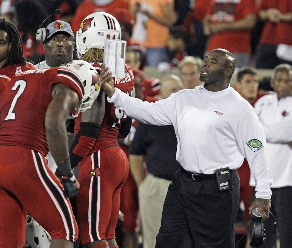 Louisville coach Charlie Strong directs his team during a timeout in their NCAA college football game against Rutgers in Louisville, Ky., Thursday, Oct. 10, 2013. Louisville remained undefeated with a 24-10 victory