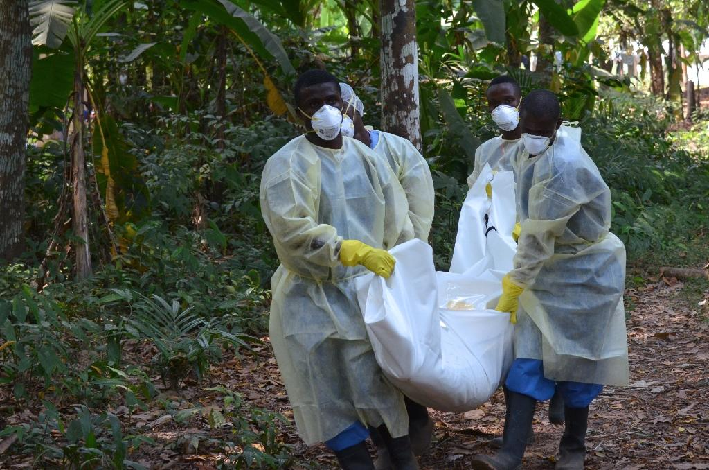 Red Cross volunteers, wearing protective clothing, carry the body of a person who died from Ebola during a burial in Monrovia, Liberia, on January 5, 2015 (AFP Photo/ZOOM DOSSO)