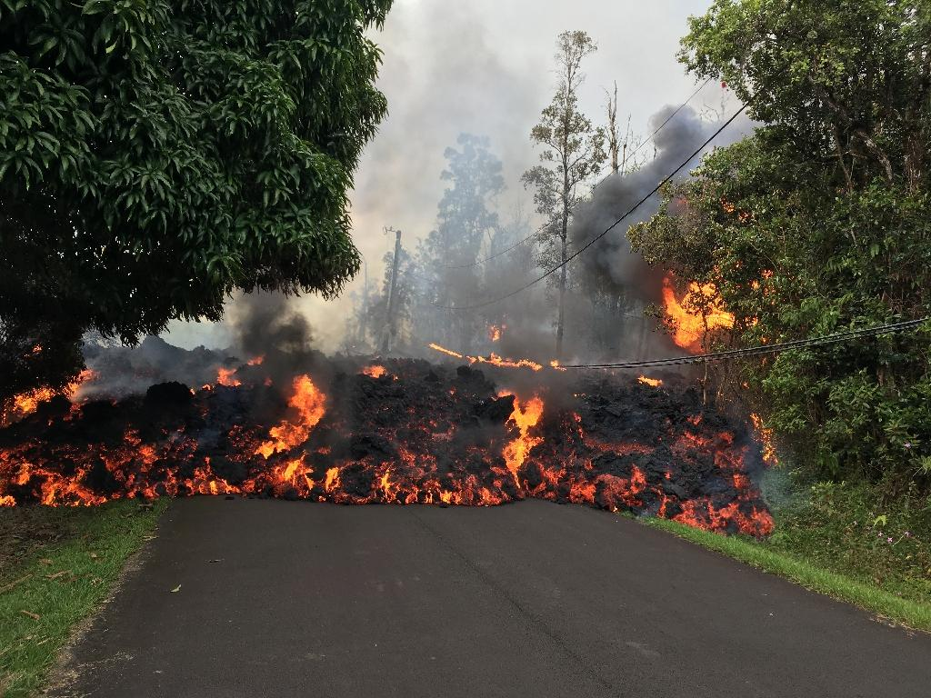 "Lava from the Kilauea Volcano flows across a street on Hawaii's ""Big Island"" (AFP Photo/)"