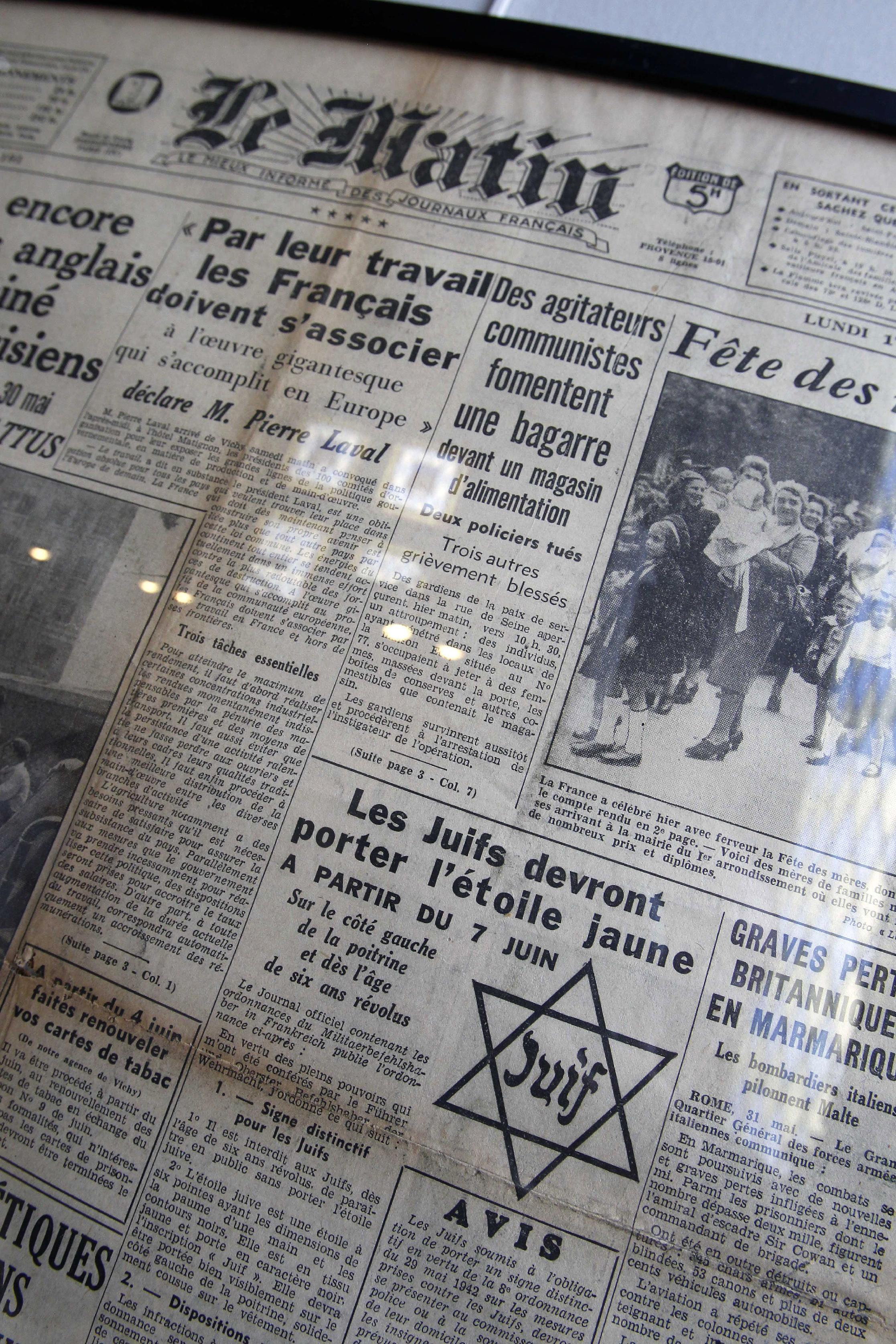 "In this photo taken Monday, July 16, 2012 shows the front page of daily newspaper Le Matin reading ""Jews must wear the yellow star starting July 7"" coming from the Archives of Paris Police Prefecture is presented for an exhibition of French archives on Shoah in Paris. The chilling archives of the biggest World War II deportation of French Jews are being opened up to public view for the first time. It coincides with the 70th anniversary of the Vel' d'Hiv roundup by Paris police of some 13,000 Jews over two days who were then sent to Auschwitz death camp. Photos, signatures and records of personal possessions from many of the victims are on display at a Paris district town hall. (AP Photo/Remy de la Mauviniere)"