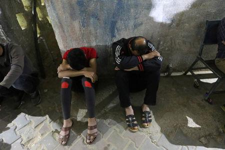 Relatives of a Palestinian Hamas militant who was killed in an Israeli air strike, react at a hospital in the central Gaza Strip May 3, 2019. REUTERS/Ibraheem Abu Mustafa